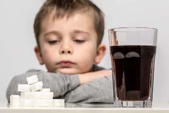 Junge vor Soft Drink, daneben Zuckerwürfel